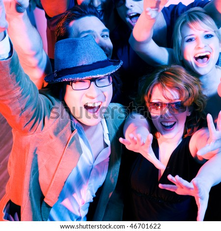 Crowd cheering - their rock idol or simply having fun in a club or disco party - stock photo