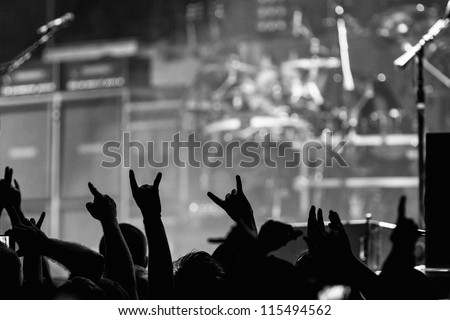 Crowd going crazy and putting up the metal horns at a rock concert - stock photo