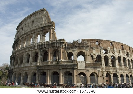 crowd in front of the Colosseum or Flavian Amphitheater , the first permanent amphitheater to be built in Rome, Italy