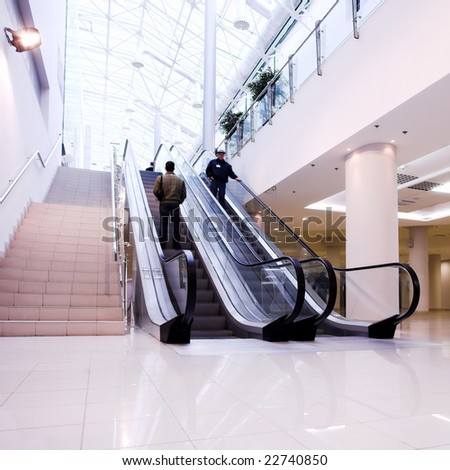 Crowd in office centre on escalator - stock photo