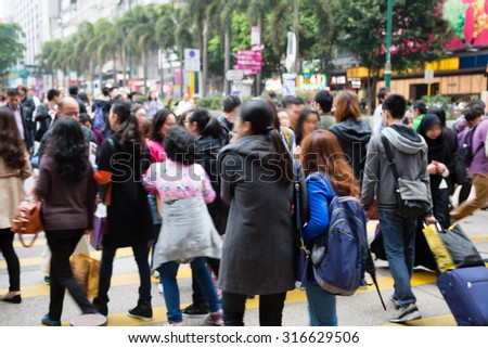 Crowd of anonymous people walking on busy Hong Kong street. Picture is not in focus. - stock photo