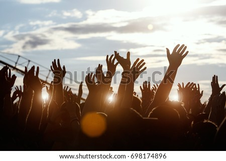 Crowd of audience with hands raised at a music festival.