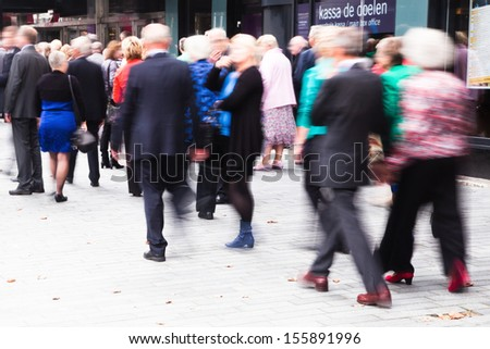crowd of dressed up people walking to a concert