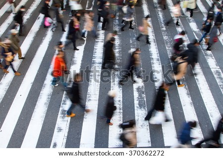 Crowd of pedestrians crossing a zebra crossing in a high angle view with motion blur and focus to the white stripes on the tarmac