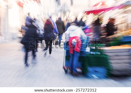 crowd of people at street market with creative zoom effect