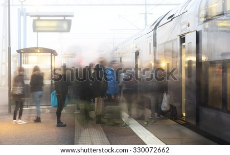 Crowd of people getting on and off train on foggy day