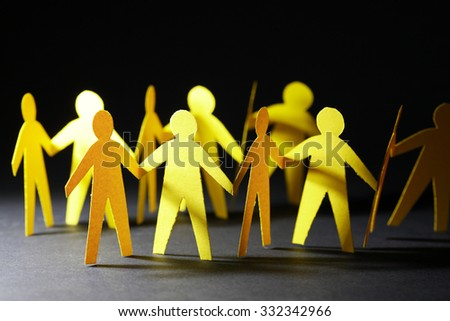 Crowd of people made from yellow paper on dark background