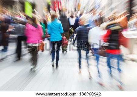 crowd of shopping people in the busy street of the city with creative zoom effect - stock photo