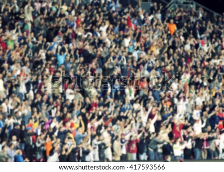 crowd of soccer fans at the stadium - defocused background - stock photo