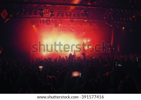 crowd silhouettes at music concert  in front of stage - stock photo