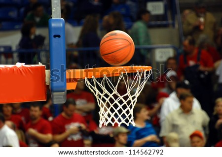 Crowded high school gymnasium watches a spinning basketball drop into the orange metal goal and white net. - stock photo
