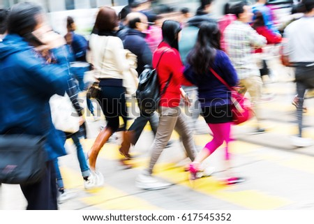 crowds of people crossing a city street in motion blur
