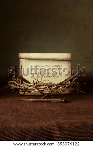 Crown of thorns and nails with John 3:16 verse over cloth - stock photo