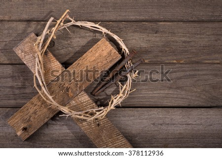 Crown of thorns with a cross and nails on a rustic wood surface