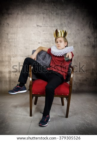 Crowned boy holding a television remote control