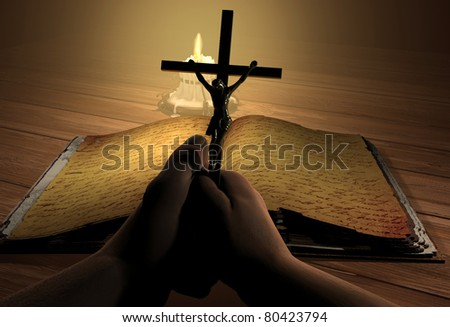 Crucifix in hand near the holy book. - stock photo
