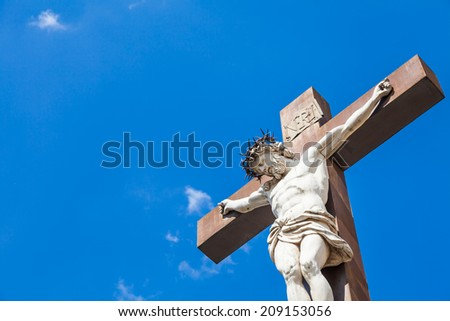 Crucifix made of marble with blue sky in background. France, Provence Region.