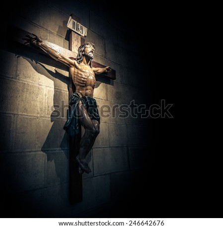 Crucifix on wall in spotlight inside old dark church or cathedral. Jesus Christ on cross. Religion, belief and hope. Holy and sacred places. - stock photo