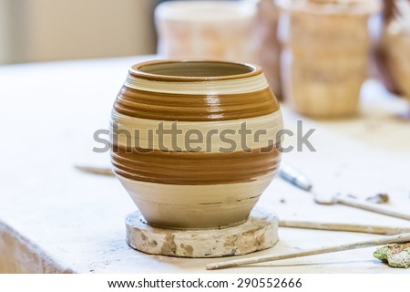 Crude clay pot on a wooden plate in outdoor workshop - stock photo