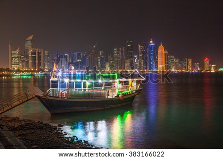 Cruise dhow and Doha downtown skyline illuminated at night. Qatar, Middle East