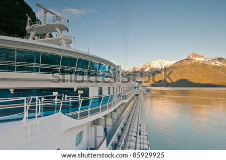 Cruise ship anchored at harbor with beautiful sunrise on background mountains. - stock photo