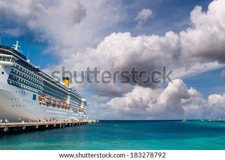 Cruise ship anchored in a caribbean port. - stock photo