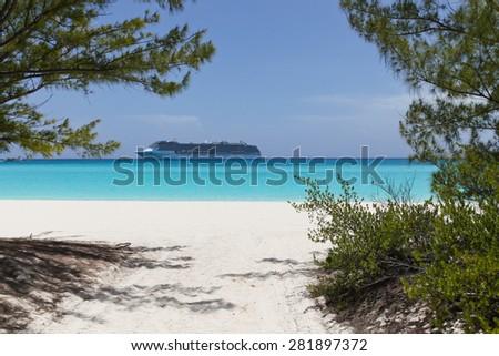 cruise ship anchored near a white sand beach on blue water - stock photo