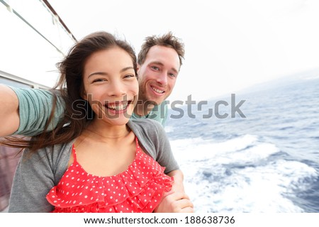 Cruise ship couple taking selfie self portrait photo romantic. Happy lovers, woman and man traveling on vacation travel sailing on open sea ocean enjoying romance. Young Asian woman and Caucasian man. - stock photo