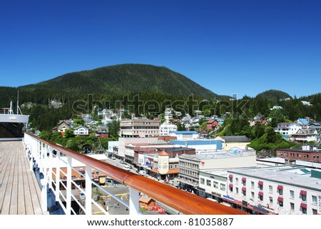 Cruise ship docked at scenic harbor overlooking vacation town - stock photo