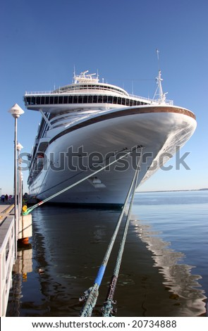 Cruise ship docked with ropes tied up - stock photo