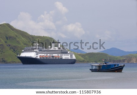 Cruise ship & fishing boat at anchor in Komodo Island Bay, Indonesia - stock photo