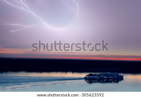 cruise ship in lightning storm at sunset - stock photo