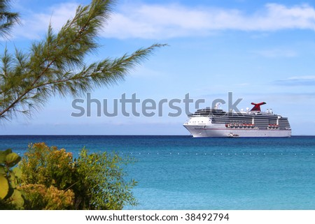 Cruise ship in the clear blue Caribbean ocean with greenery in the foreground