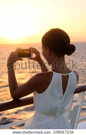 Cruise ship vacation woman taking photo with smart phone camera enjoying sunset on travel at sea. Girl using smartphone to take picture of ocean sunset. Woman in dress on luxury cruise liner boat. - stock photo