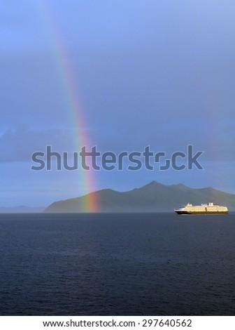 Cruise ship with a rainbow in the Gastineau Channel near Juneau, Alaska. - stock photo