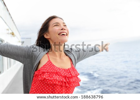 Cruise ship woman on boat in happy free pose smiling enjoying freedom. Young woman traveling on vacation travel sailing on open sea ocean. Young mixed race Asian Caucasian woman. - stock photo