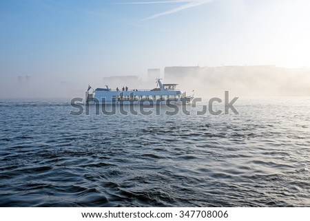 Cruiseboat in the fog in the harbour from Amsterdam in the Netherlands - stock photo