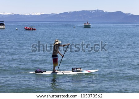 Cruising on a stand-up surfer in Lake Tahoe, CA. - stock photo