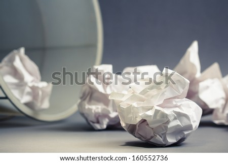 Crumble paper balls spill out of bin - stock photo