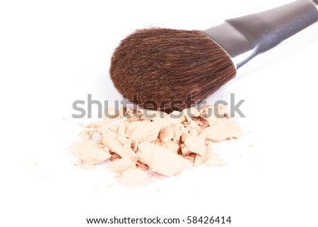 Crumbled eyeshadows with professional make-up brush, closed-up on white - stock photo
