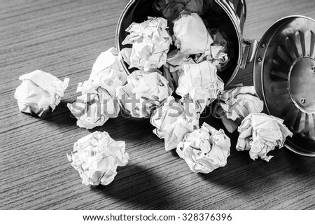 crumbled paper on wooden desk - stock photo