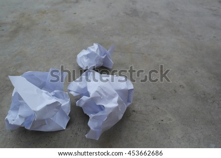 Crumbled papers on the cement floor