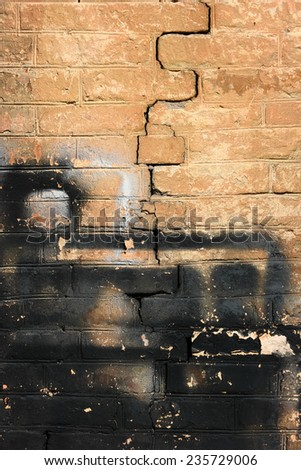 Crumbling brick wall. The shabby brick wall with a big crack.