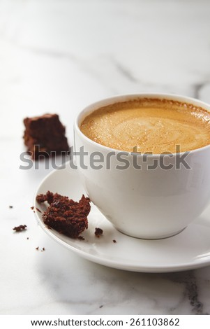 Crumbling chocolate brownie on espresso coffee cup cappuccino or latte saucer - stock photo