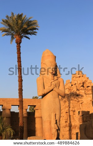 Crumbling statue at sunset  in  the most important Pharaonic site   Ancient Egypt at Karnak Temple, Luxor