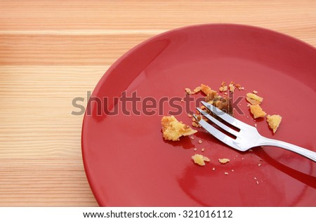 Crumbs remain from an eaten slice of pumpkin pie, with a fork on a red plate - stock photo