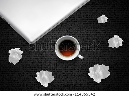 Crumpled colorful papers with laptop and coffee on black desktop. - stock photo