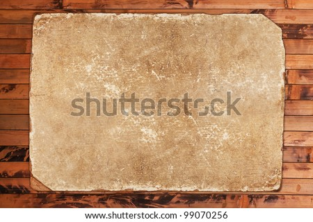 Crumpled old paper sheet on a wooden background