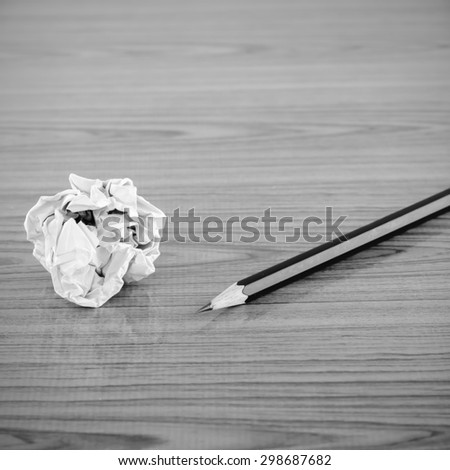 crumpled paper and pencil on wood background black and white color tone style - stock photo