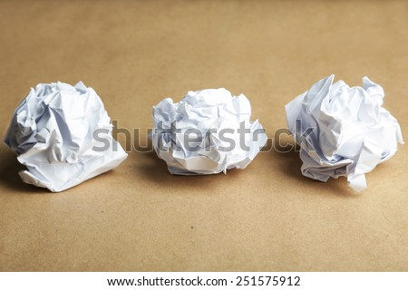 Crumpled paper ball on brown background